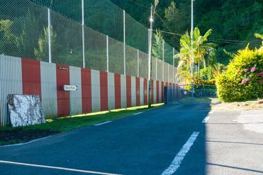 Le sentier passe entre la propriété et le stade