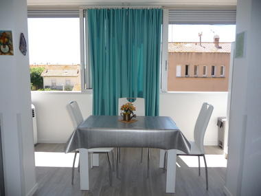 La table sur la partie balcon, intégré au studio, baies grandes ouvertes.