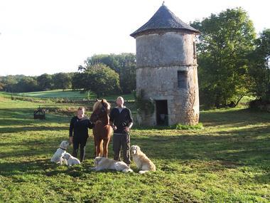 les hôtes avec leur poney et les chiens devant le pigeonnier