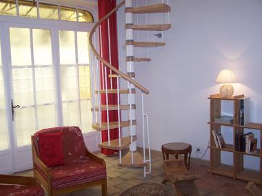 un coin du salon avec l'escalier montant à la chambre