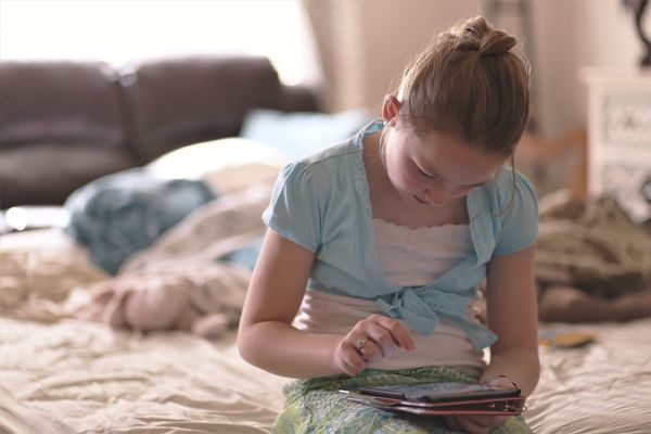 girl-sitting-on-bed-holding-tablet-computer-1313972