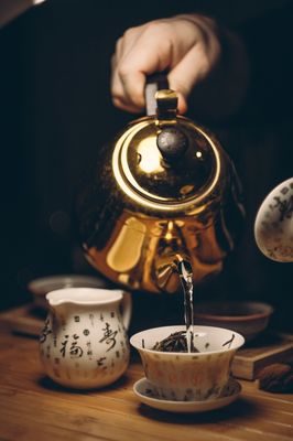 person-holding-gold-teapot-pouring-white-ceramic-teacup-230490