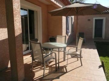 La terrasse du gîte avec salon de jardin et barbecue.