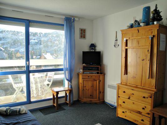 Salon, coin repas et balcon vue sur les chalets